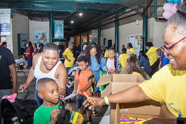 Janett Simmons (right), a parent engagement assistant at William Paca Elementary School in Landover, hands out school supplies to children attending the Prince George's County Back to School Block Party at Baysox Stadium in Bowie on Aug. 25. (Shevry Lassiter/The Washington Informer)