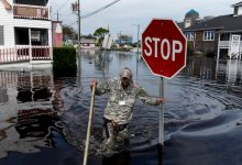 A member of a private critical crisis search and rescue team holds a stop sign as he wades through floodwaters after Hurricane Florence hit in Carolina Beach, North Carolina, on Monday, Sept. 17, 2018. (Callaghan O'Hare/Bloomberg)