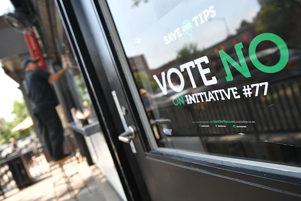 "A man stands near a ""vote no on Initiative #77"" sign on June 18, 2018 in Washington, DC. - Washington, DC's upcoming primary election includes a ballot measure called Initiative 77, a policy to gradually raise the minimum wage that tipped workers receive. (MANDEL NGAN/AFP/Getty Images)"