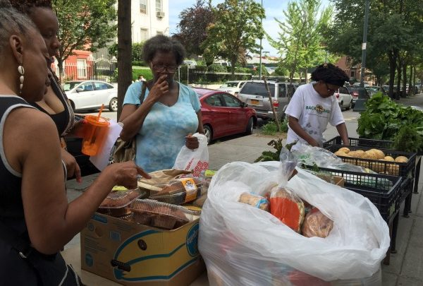 **FILE** Women participating in a church sponsored community food drive and free give-away of fresh produce and baked goods on a public sidewalk in Fort Greene, Brooklyn, NYC - August 23, 2015 (Keith Getter/Getty contributor)