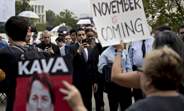 Visitors waiting in line take photographs of demonstrators outside the U.S. Supreme Court in Washington, D.C., U.S., on Tuesday, Oct. 9, 2018. Brett Kavanaugh will be at the end of the Supreme Court's bench when he hears his first argument as a justice today. He'll do so even as controversy continues to swirl over his selection by President Donald Trump and the sexual assault allegations that almost derailed it. (Andrew Harrer/Bloomberg via Getty Images)