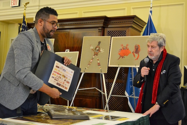 "Solomon Haile Selassie (left), production specialist at the Library of Congress who organized a 40th anniversary event for ""The Wiz,"" shows sketches from the film that are explained by Tony Walton, the movie's production and costume designer, at the Library of Congress in D.C. on Oct. 27. (Brigette Squire/The Washington Informer)"