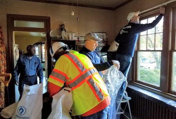 William Drew looks on as WGL and Washington Gas President and CEO prepares his windows for weatherization. Also included are WGL and Washington Gas' Chief Communications Officer Brian Edwards and longtime company Weatherization pioneer Bobby Bethea.