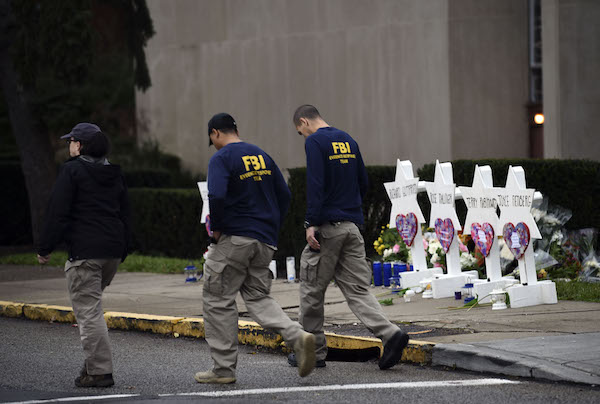 Members of the FBI walk past a memorial outside the Tree of Life synagogue after a shooting there left 11 people dead in the Squirrel Hill neighborhood of Pittsburgh on October 27. (Photo by Brendan SMIALOWSKI/AFP/Getty Images)
