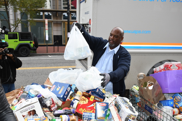 U.S. Postal Service employee Cecil Rich leaves donations at the NBC4 Food for Families drop-off area while on his mail delivery route in northwest D.C. on Nov. 19. (Roy Lewis/The Washington Informer)