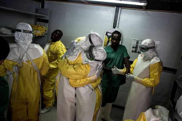 Health workers embrace whilst putting on their personal protective equipment (PPE) before heading into the red zone at a newly build MSF (Doctors Without Borders) supported ebola treatment centre (ETC) on November 7, 2018 in Bunia, Democratic Republic of the Congo. - The death toll from an Ebola outbreak in eastern Democratic Republic of Congo has risen to more than 200, the health ministry said on Nov. 10, 2018. (JOHN WESSELS/AFP/Getty Images)