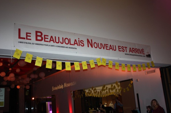 """A banner stating """"Le Beaujolais Nouveau est arrive!"""" (""""the Beaujolais Nouveau is here!"""") is displayed at the French Embassy in D.C. on Nov. 16 to mark the annual celebration of the first wine from the year's harvest. (Courtesy of Mer Events)"""