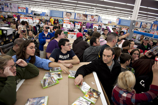 **FILE** Shoppers stand on the sidelines of a crowd that has gathered following the release of specially priced video games at a Black Friday sale at a Wal-Mart Stores Inc. store in Mentor, Ohio, U.S., on Thursday, Nov. 24, 2011. Retailers are pouring on the discounts to attract consumers grappling with 9 percent unemployment and a slower U.S. economic expansion than previously estimated. (Daniel Acker/Bloomberg via Getty Images)