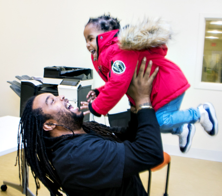 """Dontike Miller, 35, picks up his daughter Samantha, 2, from day care after his attendance at Bright Beginnings, Inc.'s """"Bridging the Gap,"""" a 12-week program that teaches fathers to manage life with their homeless families. (Shevry Lassiter/The Washington Informer)"""