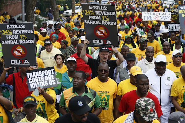 African National Congress (ANC), Congress of South Africa Trade Unions (Cosatu) and members of various civil organisations hold placards as they march to The Union Buildings in Pretoria on November 2, 2018, to protest against an e-tolling system. (Photo by Phill Magakoe/AFP/Getty Images)
