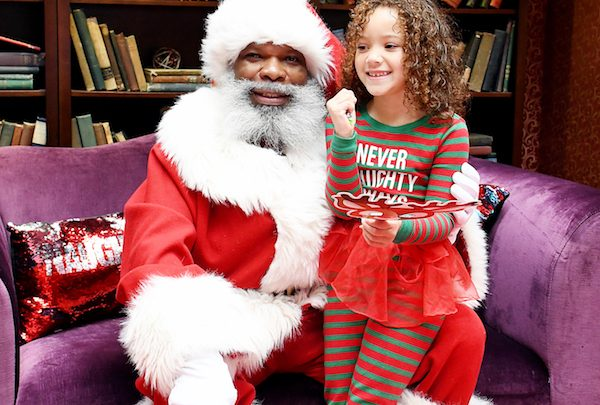 Cataleya Claros, 5, visits Fred Conlell dressed as Santa sharing her long list of gifts at the Mall at Prince George's in Hyattsville, Maryland. (Roy Lewis/The Washington Informer)