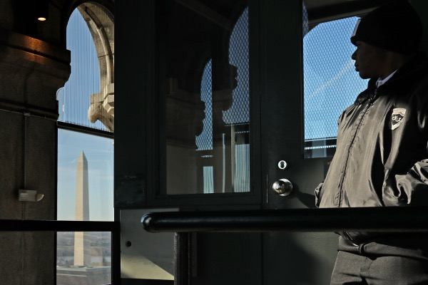 A security guard stands on the observation deck of the Old Post Office Tower in Washington, D.C., on Jan. 11, 2019. While thousands of National Park Service employees are on furlough and parks and sites are closed across the country due to the partial federal government shutdown, the General Services Administration — which leases the building and tower to the Trump International Hotel — was able to find money to pay park rangers to stay on the job. (Photo by Chip Somodevilla/Getty Images)