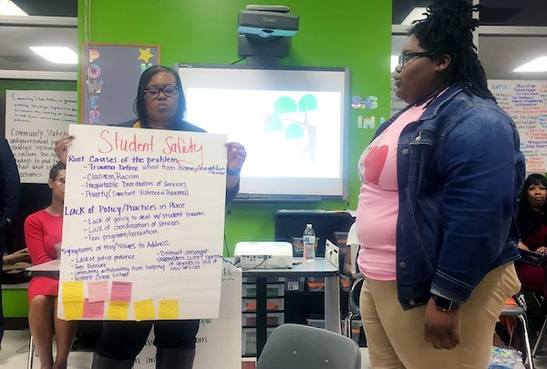 Tatiana Robinson (right), a senior at Ballou Senior High School and State Board of Education student representative, presents her group's findings at a Safe Passage and student safety roundtable at the FBR Boys & Girls Club at THEARC in Southeast on Jan. 8. (Sam P.K. Collins/The Washington Informer)
