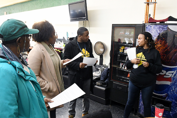 Anthony Lorenzo Green, ANC commissioner 7C04 and April Goggans of Black Lives Matter share pointers with community activists on how to canvass neighborhoods and discuss issues with residents near Nook`s Barber Shop's in northeast D.C. on Jan. 5. (Roy Lewis/The Washington Informer)