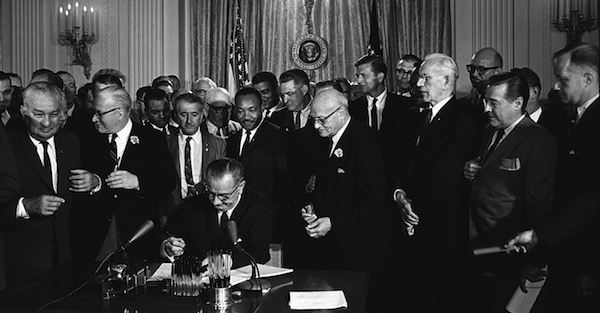 President Lyndon B. Johnson signs the 1964 Civil Rights Act as Martin Luther King Jr., and others watch on July 2, 1964. (Cecil Stoughton/White House Press Office via Wikimedia Commons)