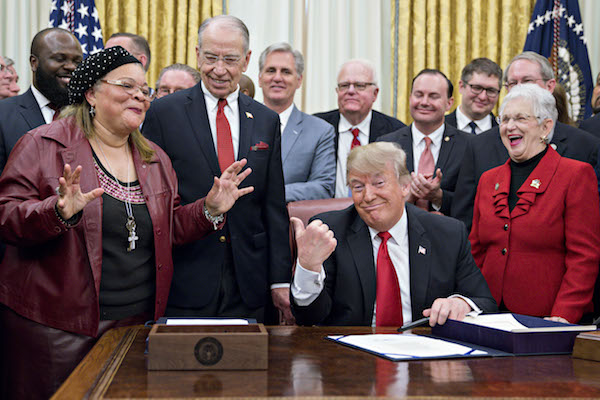 **FILE** President Donald Trump (center) gestures as Alveda King, niece of Reverend Martin Luther King Jr., speaks during a signing ceremony for S. 756, First Step Act and H.R. 6964, Juvenile Justice Reform Act with Senator Chuck Grassley, a Republican from Iowa, second left, and Representative Virginia Foxx, a Republican from North Carolina, right, in the Oval Office of the White House in Washington, D.C., U.S., on Friday, Dec. 21, 2018. (Andrew Harrer/Bloomberg via Getty Images)
