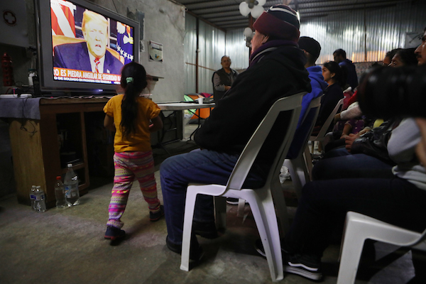 Migrants view a live televised speech by President Donald Trump on border security at a shelter for migrants on January 8, 2019 in Tijuana, Mexico. Tijuana continues to house migrants hoping to cross the border into the U.S. (Photo by Mario Tama/Getty Images)
