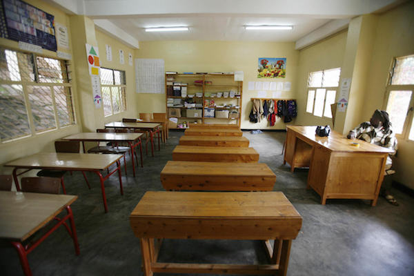**FILE** A teacher sits at her desk inside an empty classroom of the Antoine de Saint-Exupery school in Kigali, Rwanda, on Nov. 27, 2006. (JOSE CENDON/AFP/Getty Images)