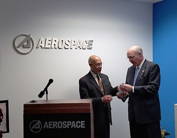 """Edward Swallows, senior vice president of civil systems group with Aerospace Corp., hands Floyd E. Holt, deputy chief administrator of the Prince George's County executive's office, glass-enclosed """"space junk"""" at Aerospace's grand opening in Greenbelt, Maryland, on Jan. 10. (William J. Ford/The Washington Informer)"""