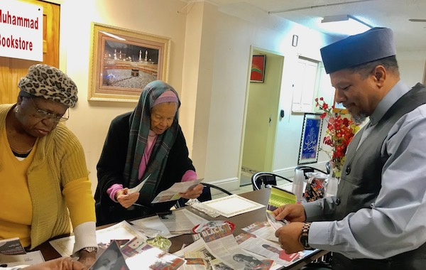 Imam Dr. Talib M. Shareef, president of the Nation's Mosque, Masjid Muhammad and two ladies peruse The Washington Informer's Black Facts column, which is being used to connect students with Black history. (Courtesy of Emma P. Ward)