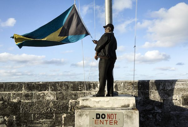 **FILE** A security guard lowers the Bahamian flag at Fort Charlotte on December 19, 2013 in Nassau, Bahamas. The fort is one of several that remain from the British colonial era. (BRENDAN SMIALOWSKI/AFP/Getty Images)