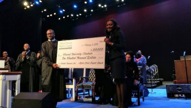 """Rev. Dr. Howard-John Wesley presents a $100,000 check for """"gap scholarships"""" to Tashni-Ann Dubroy, executive vice president and COO at Howard University, during an event at the university's Rankin Chapel on Feb. 3. (Brenda C. Siler/The Washington Informer)"""