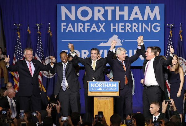 **FILE** Gov.-elect Ralph Northam (C) links arms with (L-R) current Gov. Terry McAuliffe, Lt. Gov.-elect Justin Fairfax, Attorney General-elect Mark Herring, and U.S. Sen. Mark Warner (D-VA) at an election night rally November 7, 2017 in Fairfax, Virginia. Northam defeated Republican candidate Ed Gillespie. (Photo by Win McNamee/Getty Images)