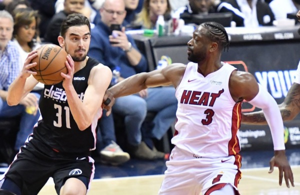 Washington Wizards guard Tomas Satoransky drives against Miami Heat guard Dwyane Wade in the first half of the Heat's 113-108 win at Capital One Arena in D.C. on March 23. (John E. De Freitas/The Washington Informer)