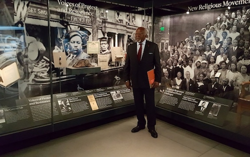 Dr. Julius Garvey stands at the exhibit of his father, Marcus Garvey, at the Smithsonian National Museum of African American History and Culture in 2016. (Courtesy of Justice4Garvey.com)