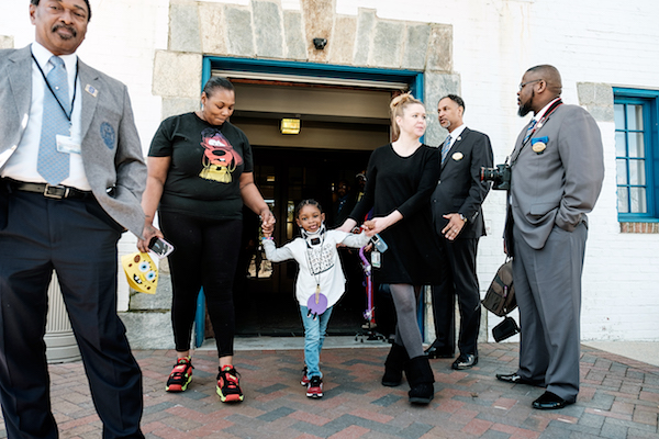 Zarnara Brown, 4, walks with members of the Masons and Eastern Star during their visit to deliver gifts to the children at the Hospital for Sick Children in in Northeast on March 16. (Michael A. McCoy/The Washington Informer)