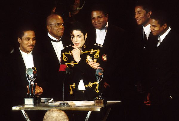 Berry Gordy Jr. of Motown Records (2nd L) with Marlon Jackson, Michael Jackson (at podium), Tito Jackson, Jermaine Jackson and Jackie Jackson of The Jackson 5, inductees (Photo by KMazur/WireImage via Getty Images)