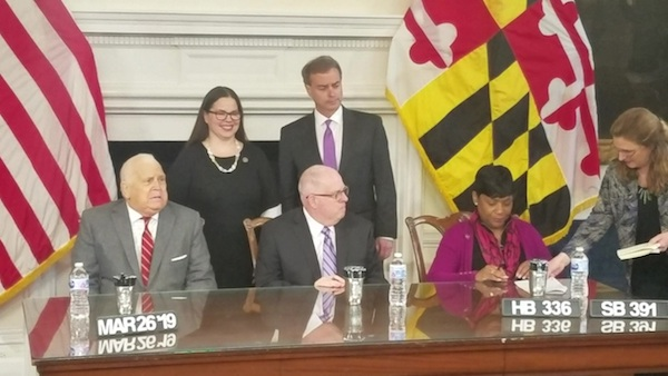 Maryland Del. Adrienne Jones (right) prepares to sign legislation into law for eligible federal workers in the state to receive unemployment benefits in the case of a federal government shutdown. Also present at the March 26 bill signing is (from left) Senate President Thomas V. Mike Miller Jr., Del. Jessica Feldmark, Gov. Larry Hogan and Sen. Brian Feldman. (William J. Ford/The Washington Informer)