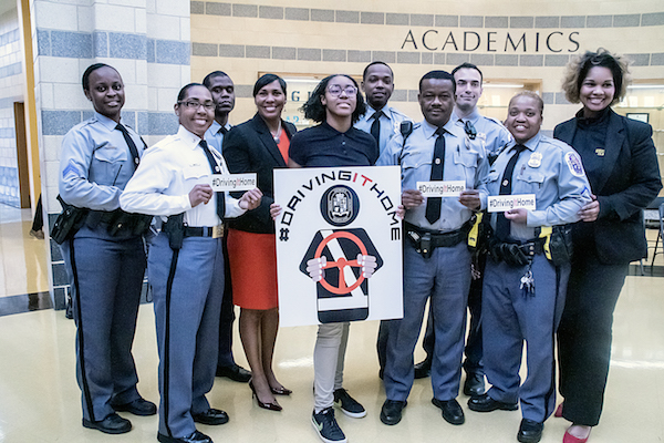 Prince George's County police officers, government officials and student representatives make a commitment to keep students safe while driving during a March 22 press conference at Oxon Hill High Schoolfor the new #DrivingItHome campaign initiative. (Shevry Lassiter/The Washington Informer)