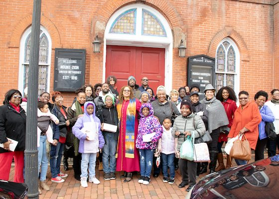 A group of Washington Informer Charities African American Heritage Tour participants gather for a photo-op after a hearty lunch in front of Mt. Zion United Methodist Church in Georgetown. (Shevry Lassiter/The Washington Informer)