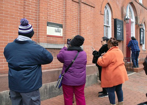 Participants of the Washington Informer Charities African American Heritage Tour of Black Georgetown hear about the rich Black history of Georgetown University, the Female Union Band Cemetery and Zion United Methodist Church on March 2. (Shevry Lassiter/The Washington Informer)