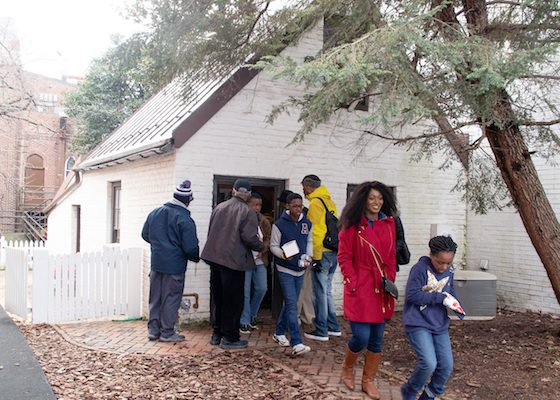 Participants in the Washington Informer Charities African American Heritage Tour move in and out of the Community House, which can hold only a few people at a time. (Shevry Lassiter/The Washington Informer)