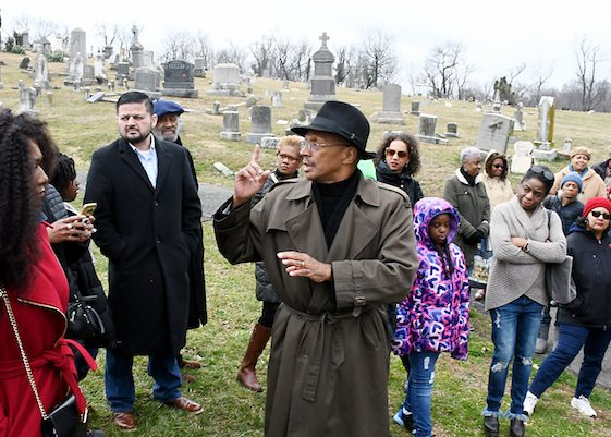 Historian C.R. Gibbs talks to Washington Informer Charities African American Heritage Tour participants about the Holy Rood Cemetery in Georgetown, the oldest burial ground of free and enslaved Africans in D.C. (Roy Lewis/The Washington Informer)