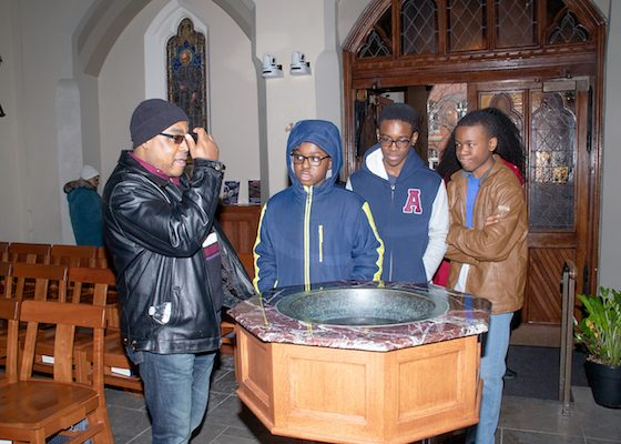 Young men learn the purpose of the bénetier in the Roman Catholic Church while attending the Washington Informer Charities African American Heritage Tour of Black Georgetown on March 2. (Shevry Lassiter/The Washington Informer)