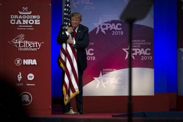 President Donald Trump hugs a U.S. flag as he takes the stage at CPAC in National Harbor, Maryland Saturday March 2, 2019. (Photo by J. Lawler Duggan/For The Washington Post via Getty Images)