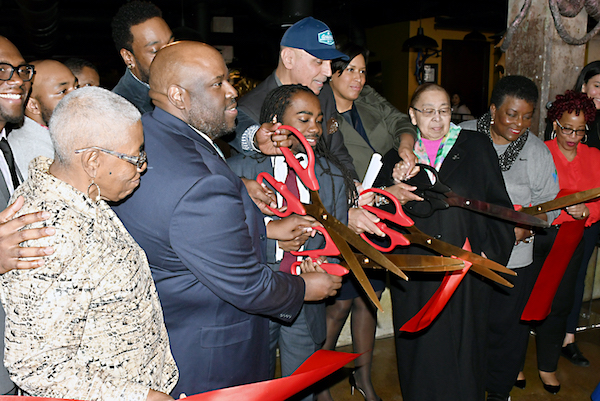 Andy Shallal, D.C. Mayor Muriel Bowser, Ward 8 Council member Trayon White and other city leaders cut the ribbon at the new Busboys and Poets location in southeast D.C, during its official opening on March 12. (Roy Lewis/The Washington Informer)