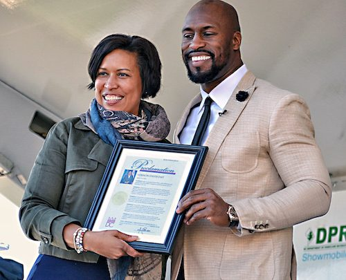 "D.C. Mayor Muriel Bowser presents a proclamation to Vernon Davis naming March 12 as ""Vernon Davis Day,"" honoring his contributions to the community at Truesdale Education Campus in northwest D.C. (Brigette White/The Washington Informer)"