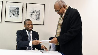 """Ivory Toldson, author of """"No BS (Bad Stats): Black People Need People Who Believe in Black People Enough Not to Believe Every Bad Thing They Hear about Black People,"""" signs a copy of his book for Ernest Green, one of the """"Little Rock Nine,"""" during an event at the National Press Club in northwest D.C. on Feb. 25. (Roy Lewis/The Washington Informer)"""