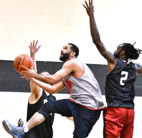 A player for the Truth team splits two Dreamcatchers defenders for a layup attempt during the Dreamcatchers' 99-94 win in the All In Hoops league championship game at the All In Hoops gymnasium in D.C. on April 20. (John E. De Freitas/The Washington Informer)