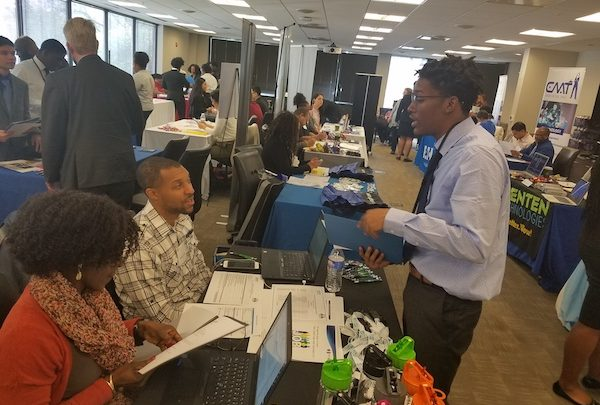 Jon Robertson (right) chats with workers at Stinger Ghaffarian Technologies of Greenbelt at the Youth CareerConnect job fair in Largo on April 12. (William J. Ford/The Washington Informer)