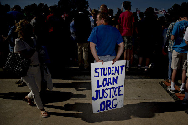 "**FILE** An attendee holds a ""Student Loan Justice"" sign while waiting for Senator Bernie Sanders, an independent from Vermont and 2016 Democratic presidential candidate, to speak during campaign rally near Robert F. Kennedy Memorial Stadium in Washington, D.C., U.S., on Thursday, June 9, 2016. President Barack Obama formally endorsed Hillary Clinton to succeed him as the next U.S. president today in a bid to unify the party two days after she secured enough delegates to clinch the Democratic nomination. (Andrew Harrer/Bloomberg via Getty Images)"