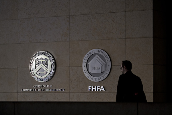 A pedestrian passes the seals of the Office of the Comptroller of the Currency (OCC) and Federal Housing Finance Agency (FHFA) at the organizations' headquarters in Washington, D.C., U.S., on Wednesday, March 20, 2019. The OCC this week fined Citibank $25 million for failing to offer some existing customers lower interest rates on mortgages or closing cost discounts that they were entitled to under a program for borrowers with a relationship with the bank. (Andrew Harrer/Bloomberg via Getty Images)