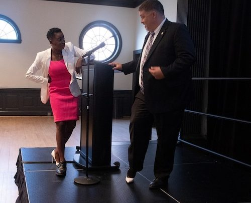 V. Glenn Fueston Jr. (right) tries on a white high heel shoe belonging to Shamere McKenzie (left), who has on Fueston's black dress shoe, as part of a lighthearted exercise during the fourth annual Crime Victims' Rights Conference at the University of Maryland's Adele H. Stamp Student Union in College Park on April 11. (Shevry Lassiter/The Washington Informer)
