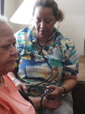 Home health care nurse Tarita Bumbray checks the blood pressure of one of her clients, Aliya Snyder, at her northeast D.C. home. (Shantella Y. Sherman/The Washington Informer)