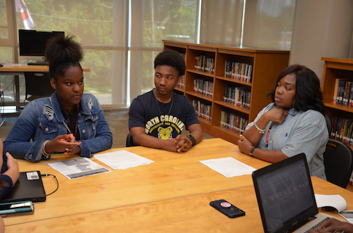 From left: H.D. Woodson freshman Natalia Givens and senior class valedictorian Tarrell Talbert discuss their progress using the D.C. Public Schools Student Guide to Graduation, College and Career with Damali Stewart, manager of postsecondary planning for D.C. Public Schools and a former Woodson counselor. (Anthony Tilghman/The Washington Informer)