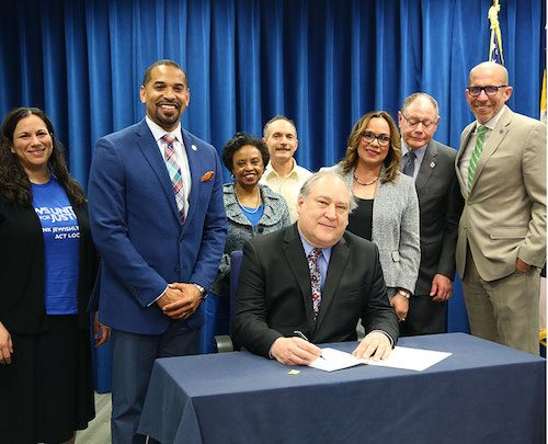 Montgomery County Executive Marc Elrich signs the Law Enforcement Trust and Transparency (LETT) Act on May 15, introduced by Council member Will Jawando (left). (Courtesy of Montgomery CountyMD.gov)